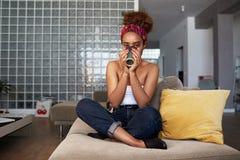 愉快的年轻美国非洲女孩用在沙发的长的卷发放松的和饮用的咖啡在现代家 免版税图库摄影