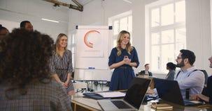 愉快的年轻老练的女性销售在现代办公室教练与不同种族的人民的带领的财务研讨会训练 股票录像