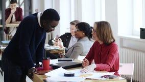 愉快的年轻非洲商人谈话与中部年迈的微笑的白种人上司妇女在现代健康办公室工作场所 股票录像