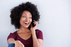 愉快的年轻非洲妇女谈话在手机 图库摄影