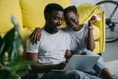 愉快的年轻非裔美国人的加上膝上型计算机和在网上购物的信用卡 库存照片