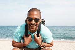 愉快的年轻非裔美国人的走在海滩的夏日的行家佩带的T恤杉和太阳镜与背包 库存照片