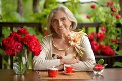 愉快的年迈的妇女饮用的咖啡 库存图片