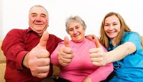 愉快的年长夫妇和年轻照料者 免版税图库摄影