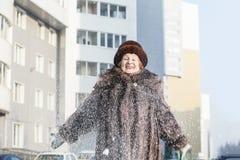 愉快的年长妇女画象皮大衣和帽子的在城市stre 库存照片