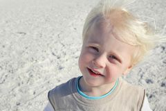 愉快的幼儿画象有风海滩的 免版税库存照片