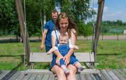 愉快的幼小快乐的三口之家在操场` s摇摆 免版税库存图片