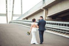愉快的庆祝婚礼之日的新娘和新郎 走开在桥梁的已婚夫妇 长科生活路概念 免版税库存图片
