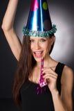愉快的庆祝有吸引力的妇女噪声制造商党帽子 免版税库存图片