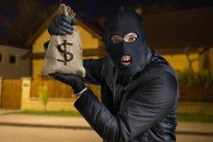 愉快的强盗或夜贼在晚上充分显示被窃取的袋子金钱 免版税库存照片