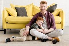 愉快的微笑对照相机的父亲和儿子,当一起时花费时间 图库摄影