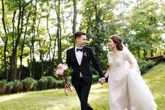 愉快的微笑新娘和新郎看彼此和跑在绿色庭院里 婚姻在夏天在公园 愉快 免版税库存照片