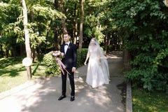 愉快的微笑新郎等待有花惊人的花束的新娘在经典衣服的与蝶形领结以绿色 免版税库存图片