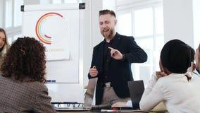 愉快的微笑的中部年迈的商人教练谈话在现代顶楼办公室会议研讨会与不同种族的小组 股票录像