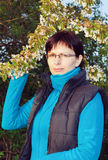 愉快的微笑的中年妇女室外与树 免版税库存图片
