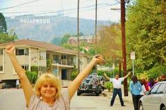 愉快的微笑的人附近的好莱坞标志 免版税图库摄影