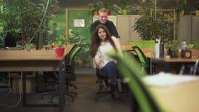 愉快的微笑的休息在工作以后的男人和妇女在现代办公室 年轻人驾驶俏丽的女孩坐办公室椅子 股票视频