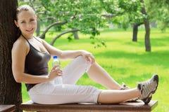 年轻愉快的微笑的体育健身妇女外面在夏天 免版税库存图片