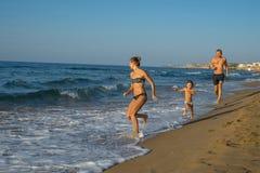 愉快的微笑的使用和跑在海滩的母亲和她的儿子 友好的家庭的概念 几天愉快的夏天 希腊 Balos 库存图片