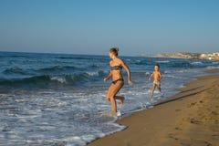 愉快的微笑的使用和跑在海滩的母亲和她的儿子 友好的家庭的概念 几天愉快的夏天 balos克利特海岛盐水湖海景 库存照片