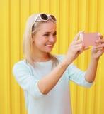 愉快的微笑的俏丽的女孩做自画象 图库摄影