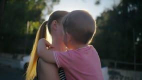 愉快的微笑的儿子拥抱并且亲吻他的妈妈 影视素材