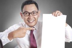 愉快的微笑的商人显示白皮书,Copyspace 免版税库存照片