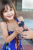 愉快的微笑的四岁的女孩在她的手上的拿着一只鸟 免版税库存照片