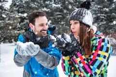 愉快的微笑的夫妇在一冬天雪天 免版税库存照片