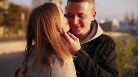 愉快的微笑的夫妇在城市,爱抚中站立并且互相亲吻 股票视频