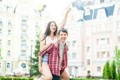 愉快的微笑的夫妇获得乐趣在夏令时的街道 免版税库存图片