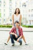 愉快的微笑的夫妇获得乐趣在夏令时的街道 免版税库存照片