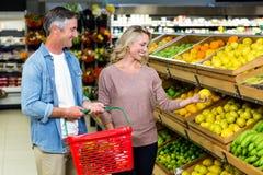 愉快的微笑的夫妇采摘柠檬 免版税库存图片