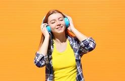 愉快的微笑的女孩听并且享受在耳机的好音乐反对五颜六色的桔子 免版税图库摄影