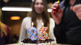 愉快的微笑的女孩吹的蜡烛在她的生日蛋糕 影视素材