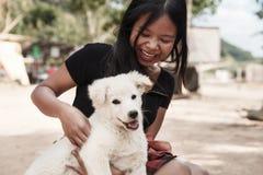 愉快的微笑的女孩在她的手上的拿着一只白色狗小狗室外 库存照片