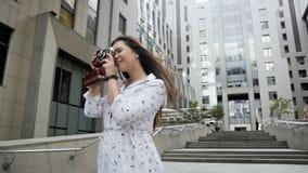 愉快的微笑的女孩慢动作录影有做与照相机的长的头发的照片 股票视频