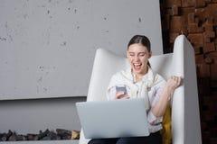 愉快的微笑的女实业家收到了在手机的一则正面消息关于成功的收养她新的项目,坐 免版税库存照片