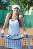 愉快的微笑的女性网球员画象法院身分的 库存图片
