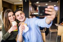 愉快的微笑的妇女和一个英俊的人享受他们的采取selfie电话的可口和鲜美汉堡和doner 库存图片