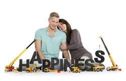 愉快的微笑的妇女和人大厦幸福词。 免版税库存照片