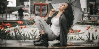 愉快的微笑的妇女在伞下在雨中 免版税库存照片