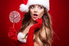 愉快的微笑的妇女在圣诞老人圣诞节服装 免版税库存照片