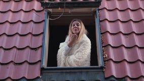愉快的微笑的妇女在家看照相机和送亲吻的窗口里 股票视频