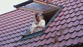 愉快的微笑的妇女开窗口并且偷看外部享受早晨 股票视频