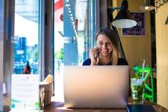 愉快的微笑的妇女生活方式博客作者有在手机的滑稽的交谈在手提电脑的距离工作期间 库存图片