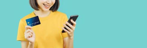 愉快的微笑的妇女藏品智能手机和信用卡 库存照片