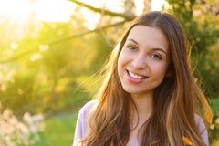 愉快的微笑的妇女身分画象在晴朗的夏天或春日外面,看您的逗人喜爱的微笑的妇女,有吸引力 图库摄影