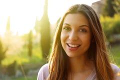 愉快的微笑的妇女身分画象在晴朗的夏天或春日外面 看对边的逗人喜爱的微笑的妇女被过滤 免版税库存图片