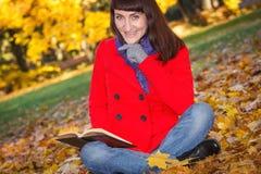 愉快的微笑的妇女阅读书在秋天公园 库存图片